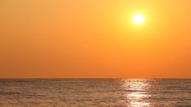 západ slunce proti oranžové nebe nad klidné mořské vlny