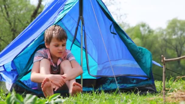 Boy with bare feet sits in tent at forest
