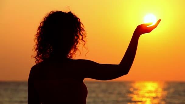 giovane donna in piedi sulla spiaggia, guardando il tramonto