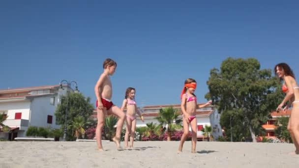 donna in bikini con i bambini giocare a nascondino e cercare sulla spiaggia