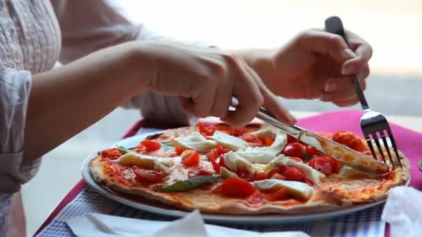 ruce ženy řez pizza s nožem a vidličkou