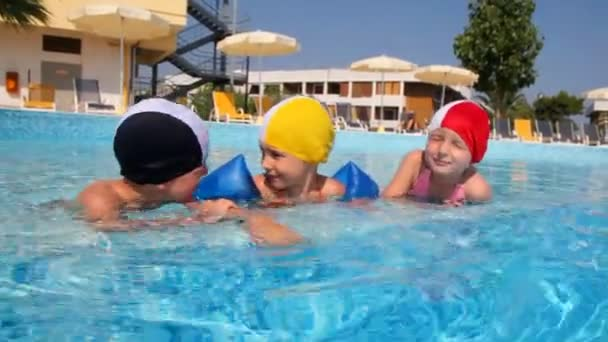Boy and girls in swimming caps are talking in the pool