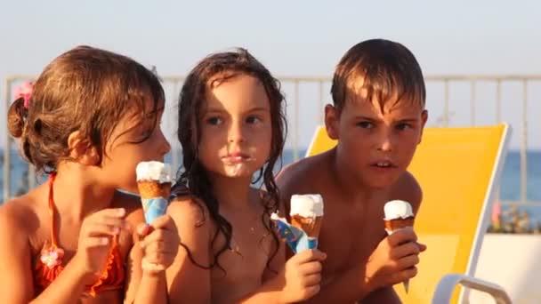 Three kids eat ice cream in waffle cone