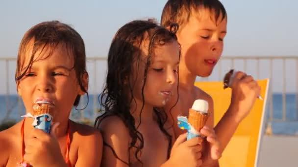 tři děti jedí zmrzlinu v vafle kužel a mluvit