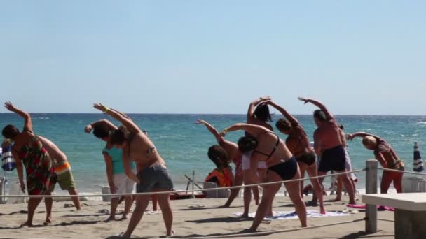 Tourists making aerobics on beach