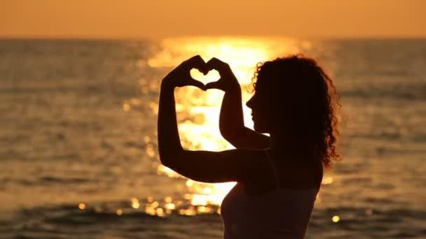 žena stojí na pláži a zobrazuje srdce formulář s pomocí rukou proti západu slunce