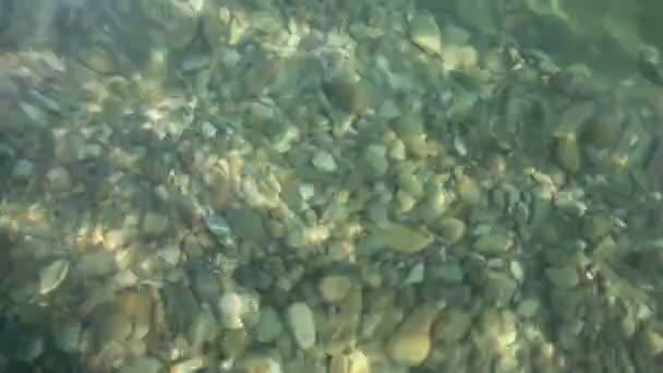 sluneční světlo se hraje na oblázky pod zvlněná vodní hladiny moře