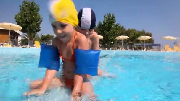 dívka a chlapec pohybující se podél hranice v bazénu po jednom