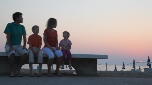 Parents and kids are sitting on bench and watching sunrise