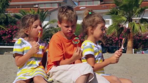 Tree kids eating lolly candy sitting on sand