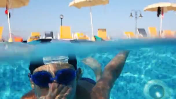 Junge mit Brille zum Schwimmen taucht in Pool und schwimmt