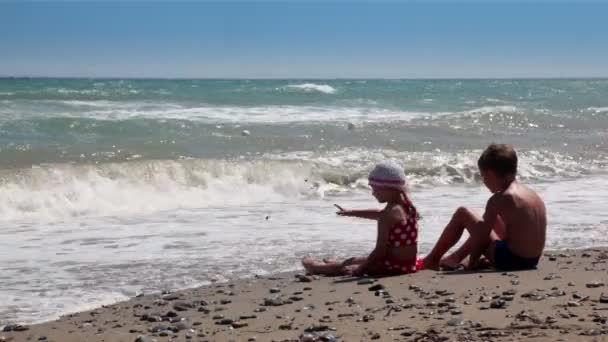 Two children looking at the waves and throw rocks into the water