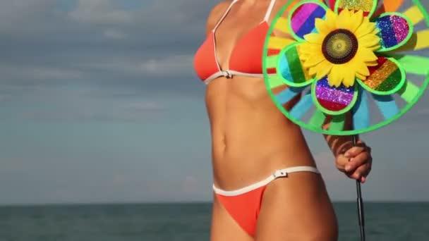 Frauenkörper mit einem farbigen Spielzeug, das sich dreht