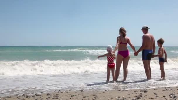 rodiče a děti stojí ruku v ruce, pak spusťte do moře