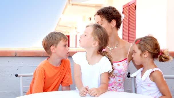 žena a tři děti sedí u balkónu