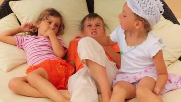 tři děti leží na polštáři v posteli a mluví