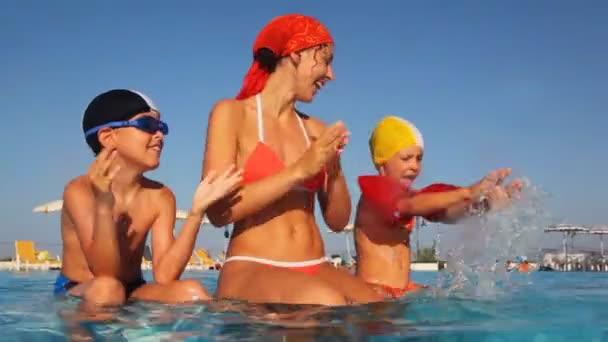 Mutter mit Kinder sitzen auf Pools Abschnitt, klatscht in die Hände