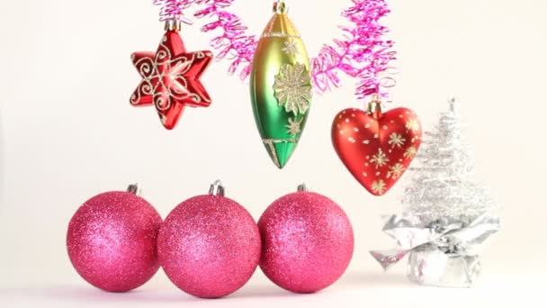 Christmas-tree decoration swing on tinsel, christmas tree balls lie below and Silver artificial Christmas tree stay