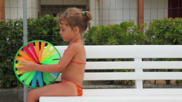 malá holka sedí na lavičce s barevnými hračkou v rukou