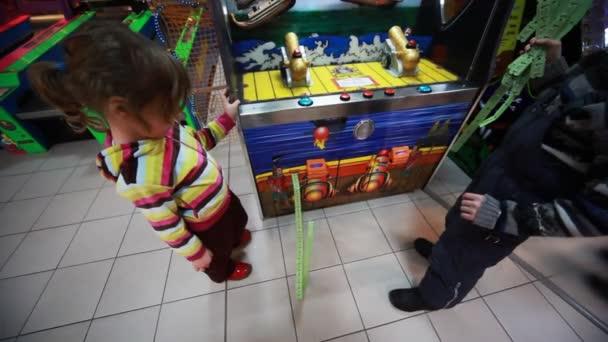 Fiú és lány, várjon, amíg a pénznyerő automata nyomtatási rengeteg kupon