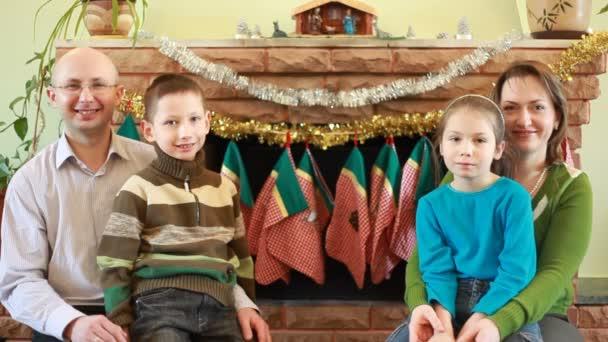 bratr a sestra sedí s rodiči před krb