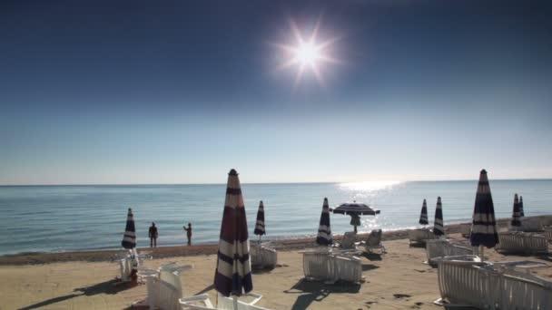 slunečníky a lehátka na pláži, turisté stojí ve vodě a making Foto