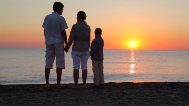 genitori e figlio in piedi sulla spiaggia tenendosi per mano
