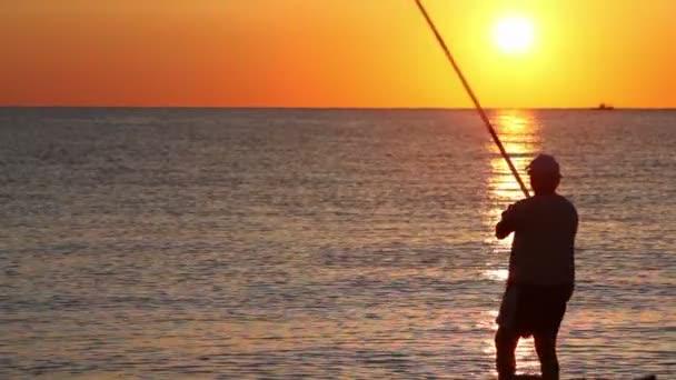 muž vrhá rybářský prut a pak vábí ryby