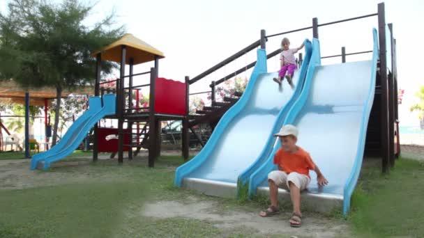 dvě děti jsou na hřišti objektu, chlapče, sjíždění