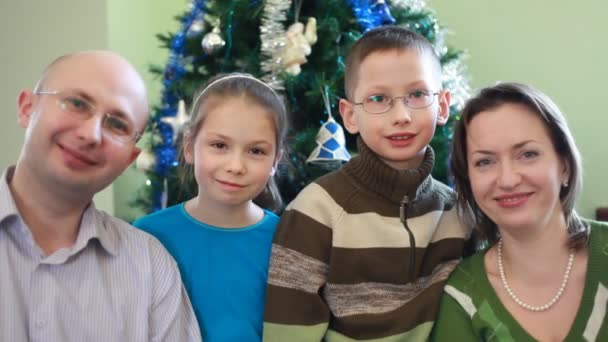 Friendly family of four sitting near Christmas tree