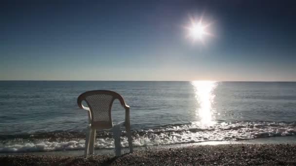ein Stuhl steht im Wasser, das von der Brandung angespült wird