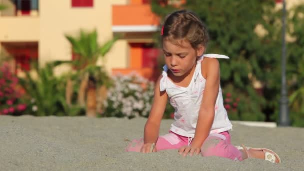 Little girl sitting on sand and writing on it