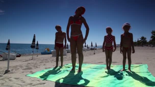 Asszony és a gyerekek állandó strand és tilt fejét