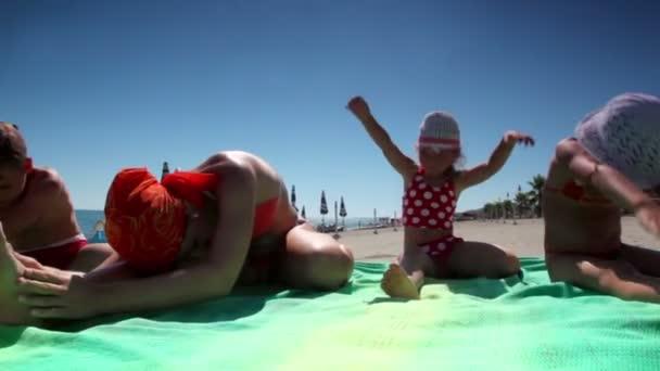 žena a děti sedí na pláži a dělat svahy