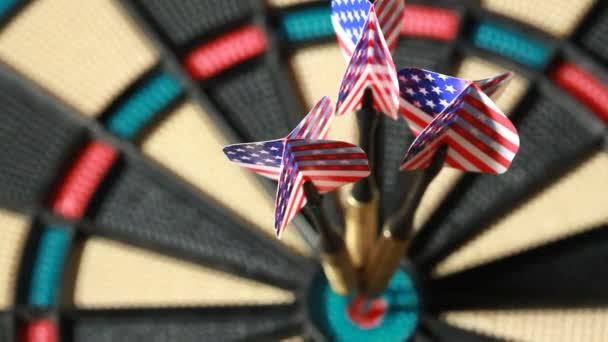 Three arrows with American flag hit bullseye on dartboard
