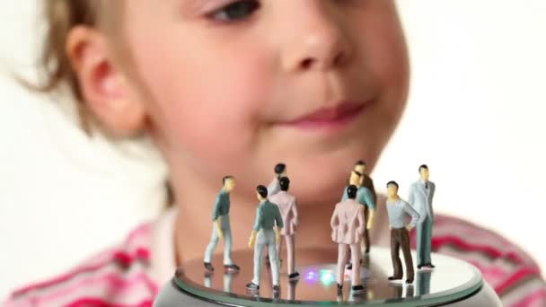 Girl holds toy figurines of women
