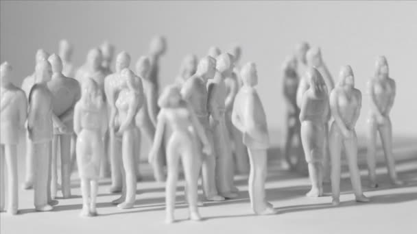 Gruppe kleiner unbemalter Spielzeugmänner und -frauen stehen und werfen Schatten