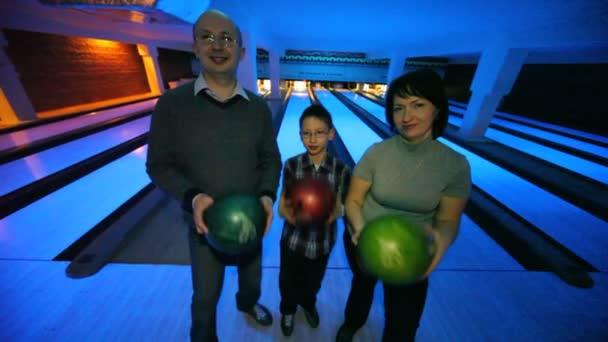 rodina tří pobytu s míčky v rukou v bowling Clubu
