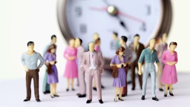 Gruppe kleiner Spielzeugmänner und -frauen steht vor großer Uhr