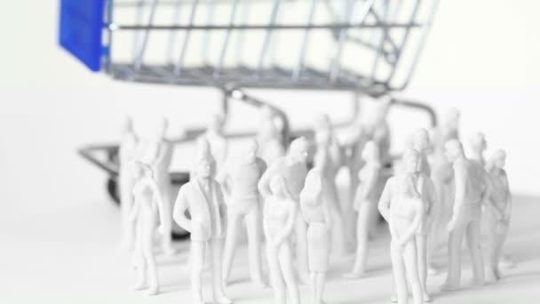 malé bezbarvé hračka mužů a žen stojí před velkou nákupní vozík
