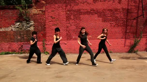 Four girls active dance synchronously and move closer