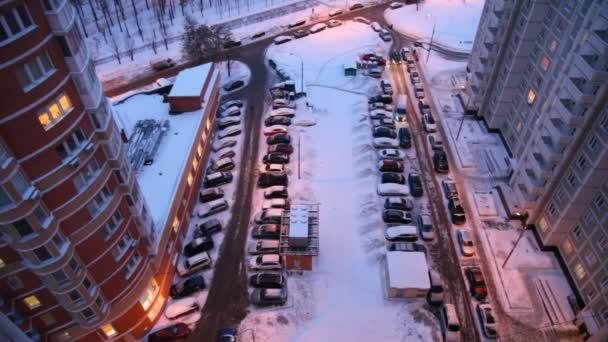 pohled shora dolů na nádvoří plné aut