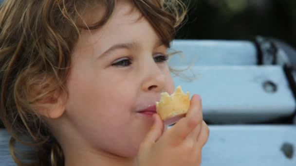 holčička jíst zmrzlinu a sedět na lavičce v parku
