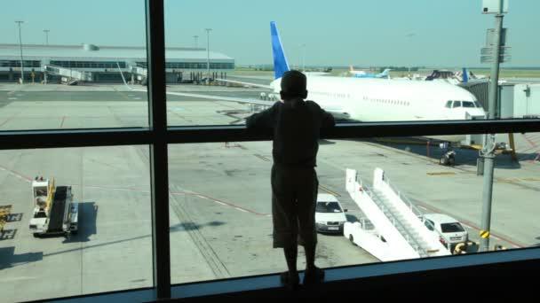 silhouette del ragazzo guarda attraverso la finestra a aerei allaeroporto