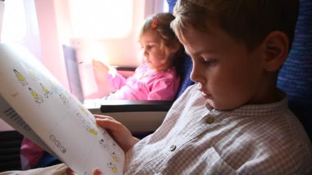 jungen und Mädchen lesen Verhaltensregeln Sicherheitshinweise im Flugzeug