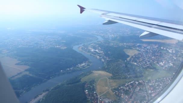 pohled z okna na křídle letadla létání nad Prahou a řeka vltava