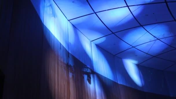 modré světlo projektorů se pohybuje na strop
