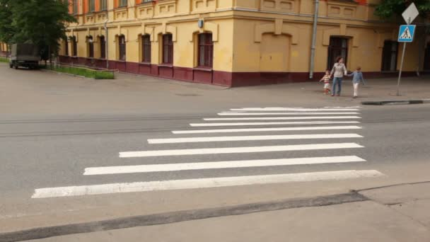 Mother and children are at pedestrian crossing road behind them on road