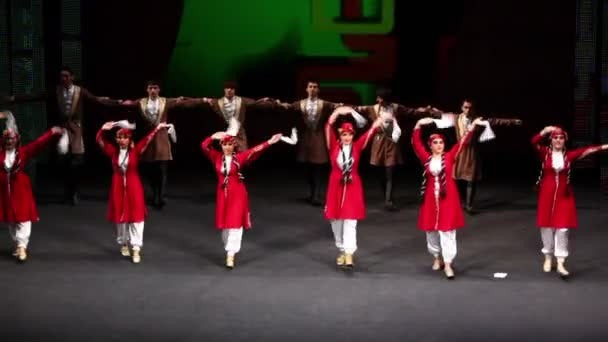 Boys and girls in caucasian costumes dance on scene
