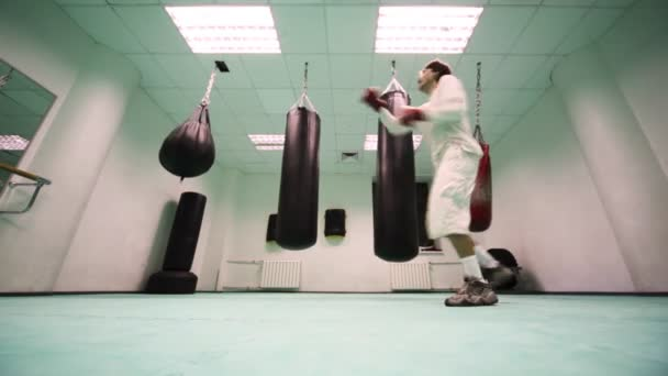 Man in gloves jumps and punches on three punchbag at boxing gym